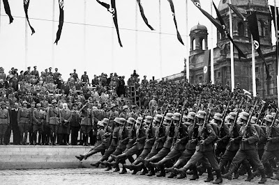 A dense formation of Nazi soldiers march past an organized crowd standing in rows. Everyone is uniformed and the street is lined with swastika flags. Black and white.
