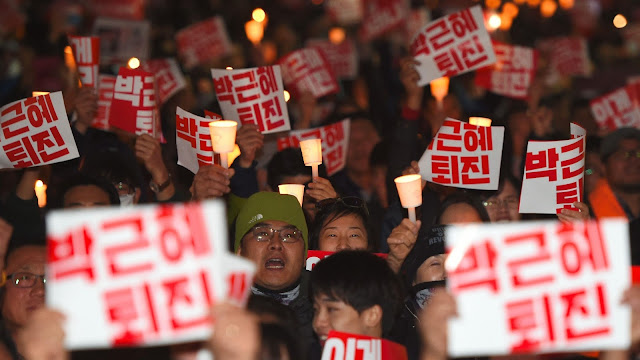 """Manifestantes surcoreanos sostienen carteles que dicen: """"Abajo, Park Geun-Hye!"""", en una marcha de protesta en el centro de Seúl, 29 de octubre de 2016."""