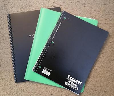 A Rocket book reusable notebook, a 3 ring paper folder, and a spiral notebook