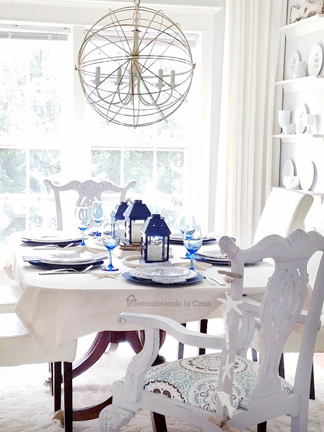 white and blue summer decor in dining room, sphere chandelier, blue lanterns, painted Chippendale chairs