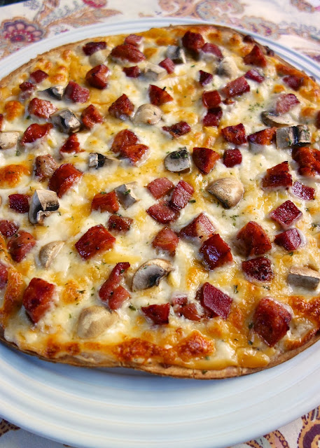 Ritz Carlton Cajun Flatbread - one of the best things we ate in NOLA! Pre-made pizza crust topped with a béchamel sauce, andouille sausage, tasso ham, mushrooms and cheese. SO good. So glad the hotel gave me the recipe!