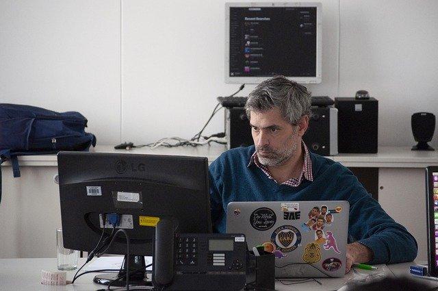 Pria dengan serius duduk didepan komputer