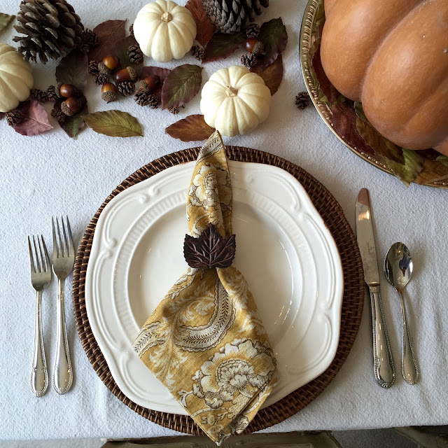 traditional fall tablescape with white plates, acorns, pine cones and pumpkins