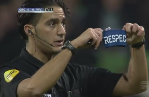 Referee Serdar Gözübüyük shows his 'Respect' armband to Groningen coach Robert Maaskant