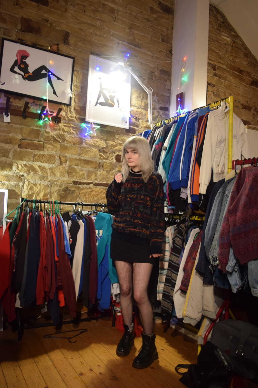 silver haired girl wearing vintage jumper in a vintage shop