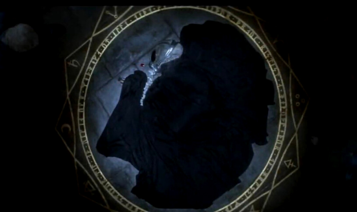 Imagem de capa: fundo escuro com cena do teaser trailer em que vemos o personagem Morfeus com o seu elmo que parece o crânio de um elefante e vestes pretas caído em um círculo dourado rodeado por runas e sigilos mágicos.