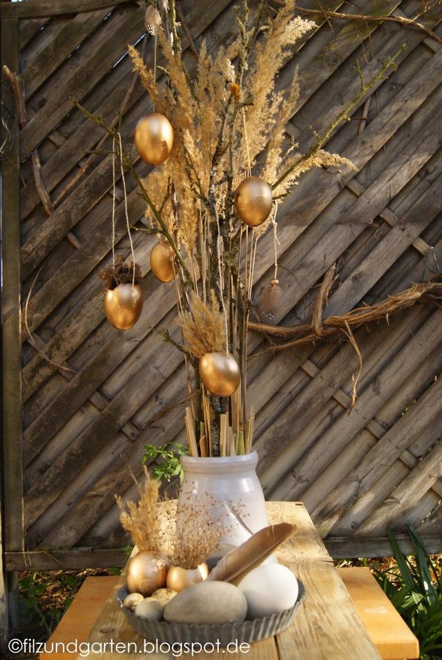 Osterdekoration mit Gräsern und goldenen Ostereiern