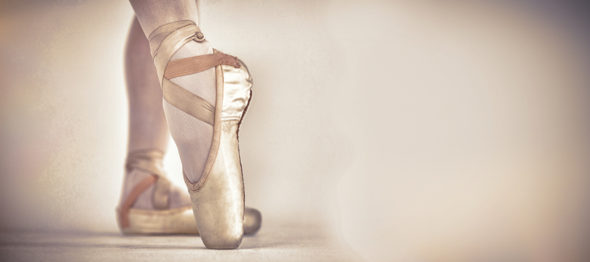 A ballerina on her tiptoes wearing pink pointe shoes.
