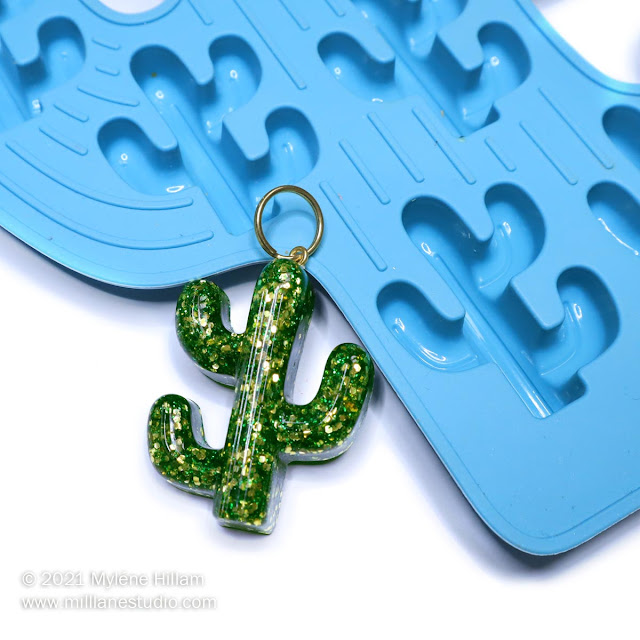 Resin cactus keychain filled with green and gold glitter sitting on the edge of a blue cactus shaped ice cube tray.