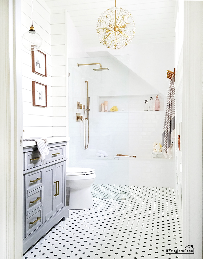 White bathroom with shiplap on wall and ceiling with gold accents