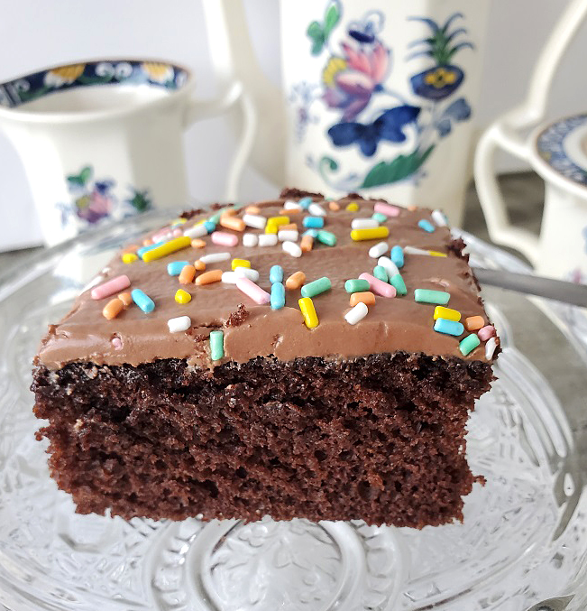 this is a sliced of chocolate cake with chocolate frosting and sprinkles made from scratch with blue and pink flowered tea set in the background
