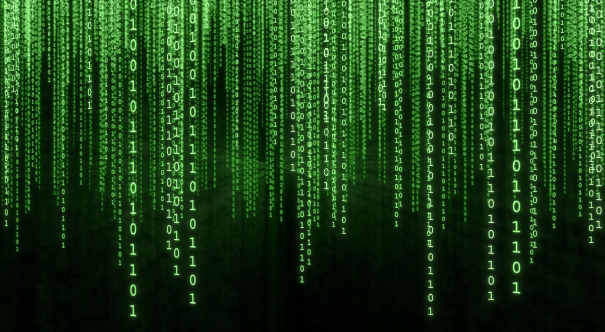 A green binary matrix illumined against a computer screen.