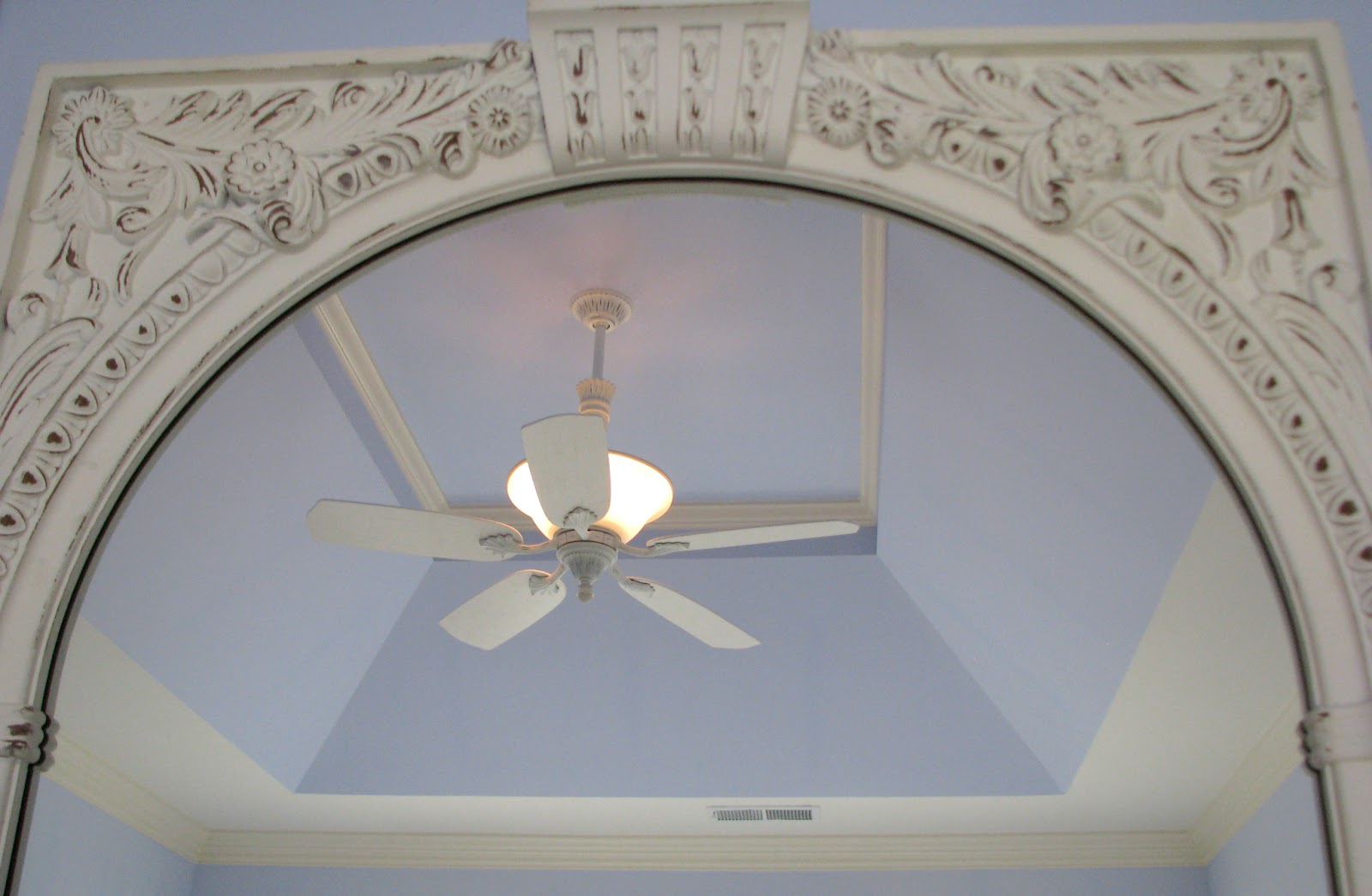 Winter white decorative ceiling fan in master bedroom with trey ceiling