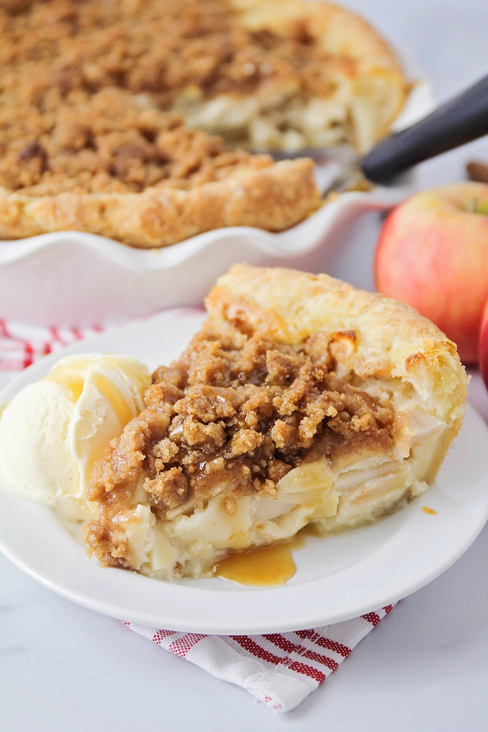 This sour cream apple pie is irresistible! It has tender apples in a sweet custard, with buttery cinnamon streusel and flaky pie crust.