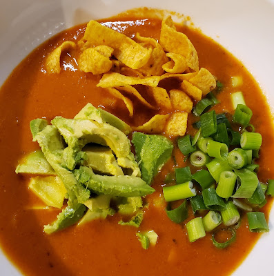 a bowl of tortila soup topped with avocado, green onions, and corn chips