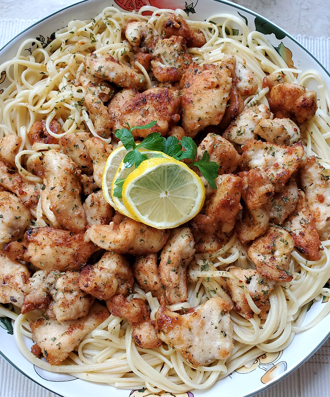 this is chicken scampi in a large Italian bowl with pasta in the bottom and lemons on top