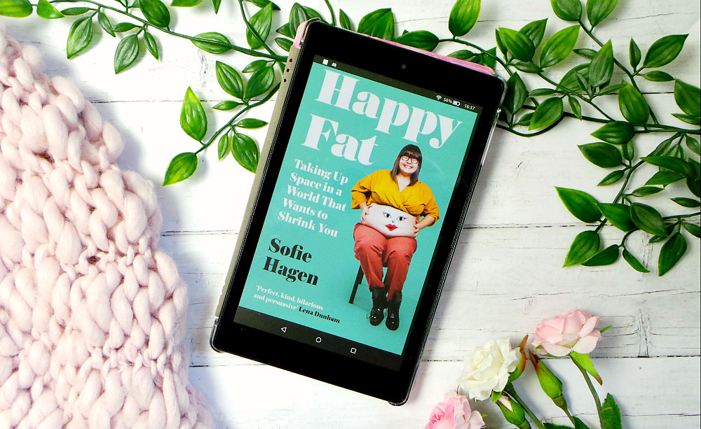 kindle fire showing the cover for happy fat next to a pink chunky knit blanket and some roses. The cover shows Sofie sat on a chair wearing a yellow crop top and red trousers with a face drawn on her stomach