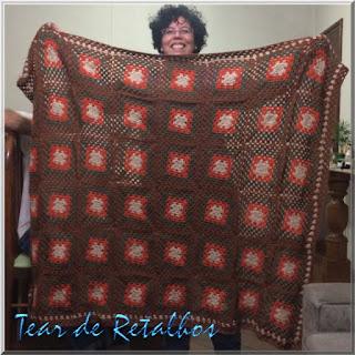 """Manta de crochê para sofá feita pela técnica dos """"quadradinhos da vovó""""."""