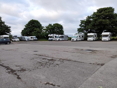 A large car park with motorhomes all parked up along the far edge.
