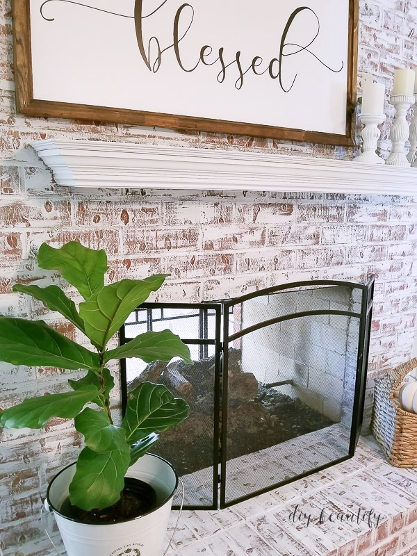 White chalk paint covers red brick fireplace | diybeautify.com