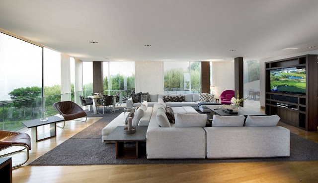 Large modern living room with white furniture and floor to ceiling windows