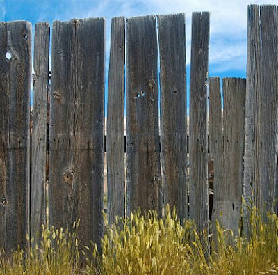 An old rickety looking wooden picket fence.