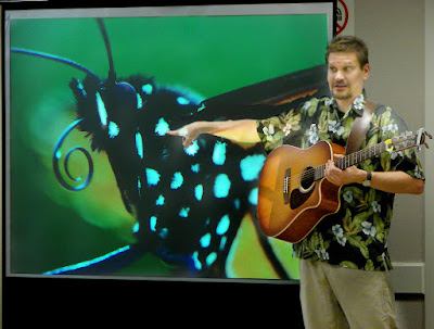 Lucas with guitar, pointing at image of monarch butterfly