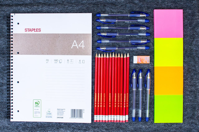 a flat lay of Staples Stationery including an A4 notepad, pencils, navy gel pens, rubber and post it notes