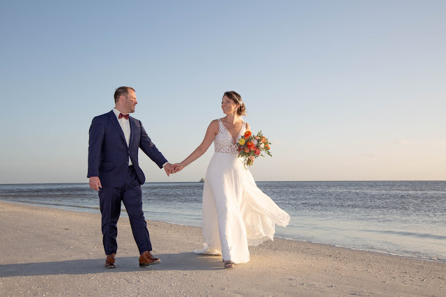 Candid photos of bride and groom walking together holding hands
