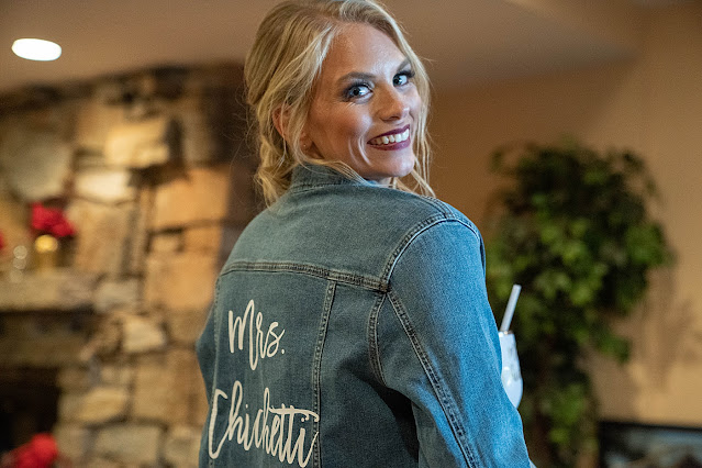 Bride showing off personalized jean jacket with new last name on it Magnolia Farm Asheville Wedding Photography captured by Houghton Photography
