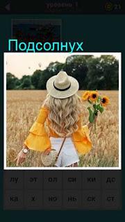 девушка идет по полю в шляпе и держит в руках подсолнух