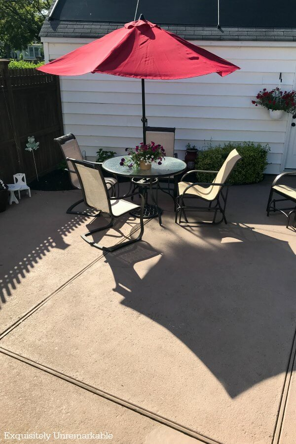Patio set with red market umbrella on painted patio