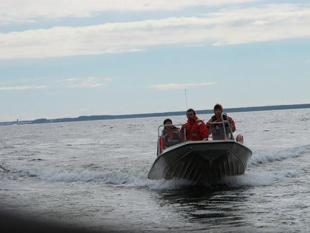Kolme henkeä veneessä pelastautumispuvuissa ja paukkuliiveissä