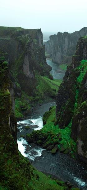 خلفية نهر ينساب بين التلال الخضراء