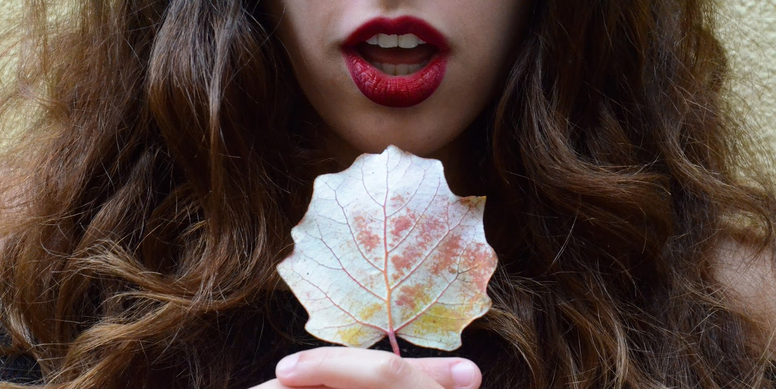 Woman with long brown hair and red lipstick holding an autumnal leaf