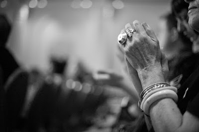 Black and white image of hands folded in prayer or clapping.