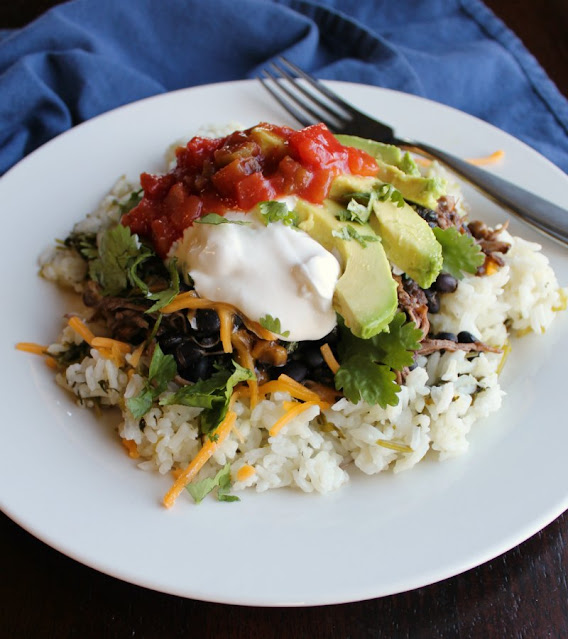 burrito bowl consisting of rice toped with salsa chicken, avocado, sour cream, salsa and more