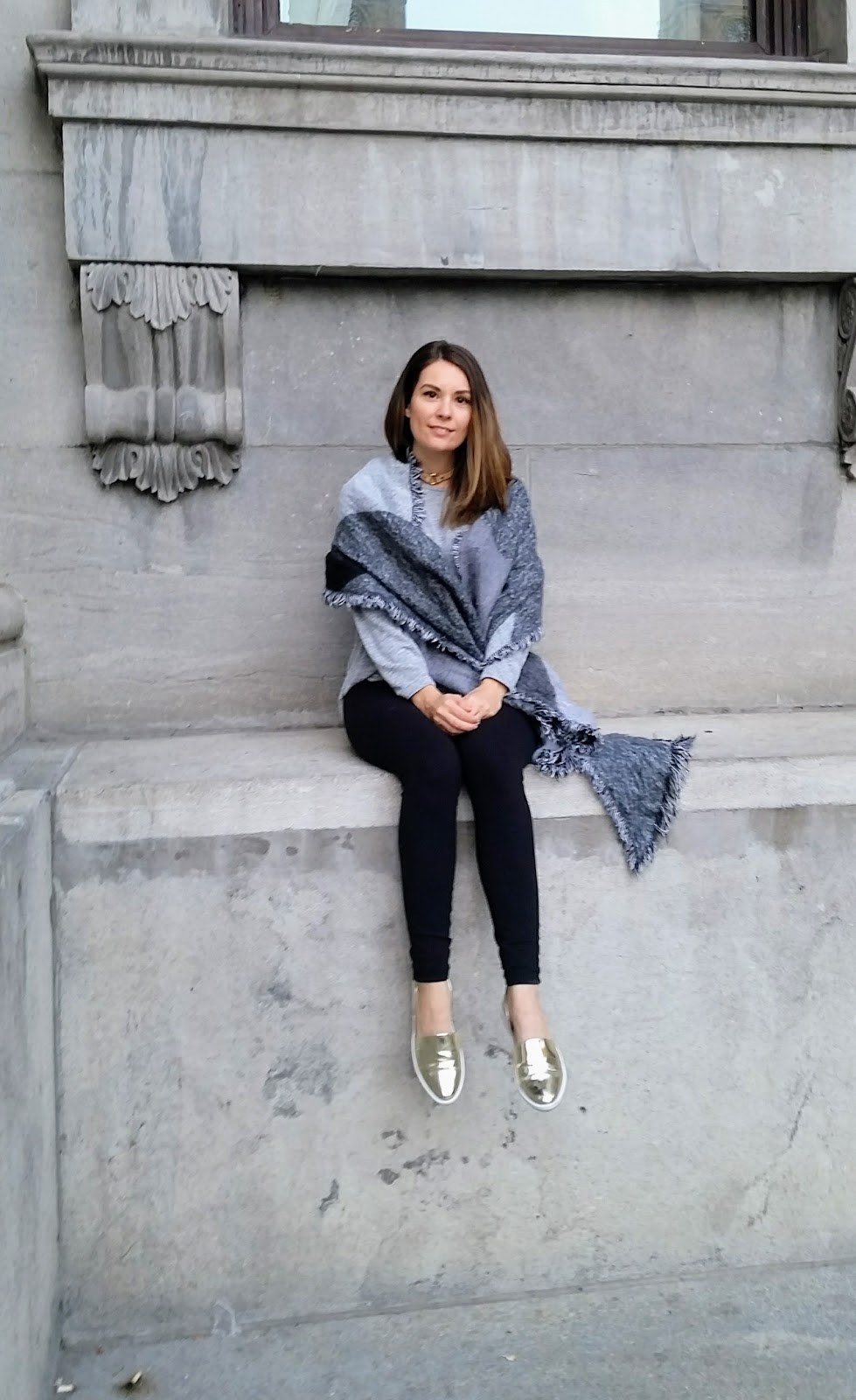Oversize grey scarf, grey sweater, black leggings, gold flats