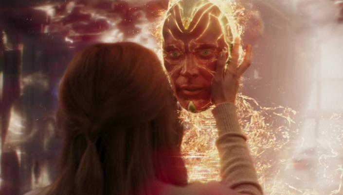 Imagem: Vemos Wanda de Costas com a mão levantada segurando a cabeça de visão. Visão é um robô meio humano meio máquina porém ele está com um olhar preocupado e um brilho do resplandece através dele que o faz desaparecer e agora só aparece sua cabeça flutuando no ar.