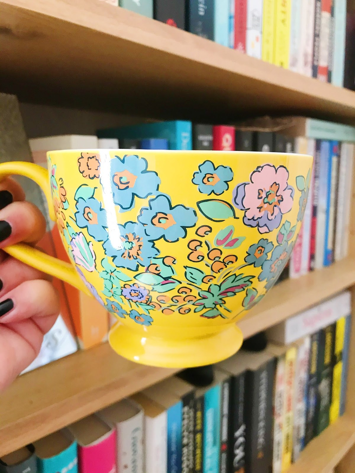 Yellow mug held up in front of bookshelf