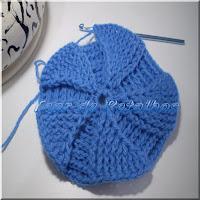 Foto mostrando uma peça sendo feita em crochê e uma agulha de crochê posicionada no trabalho.