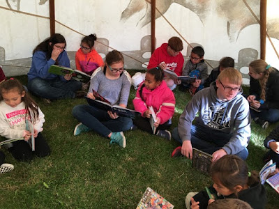 photo of high school students reading to elementary students inside teepee