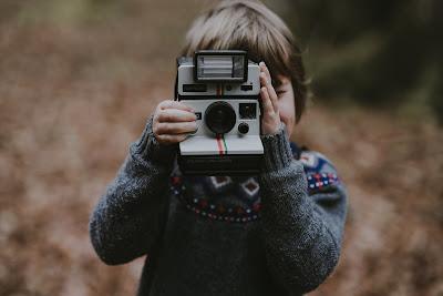 Niño con cámara instantánea