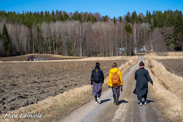 Kolme naista kävelee rinnakkain pellon laidalla kulkevaa kapeaa tietä pitkin. Traktori kyntää taustalla peltoa.