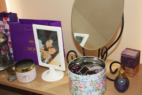 a close up of the top of a bookshelf, with a lantern, a mirror, some perfume bottles, a jewellery box, and a candle