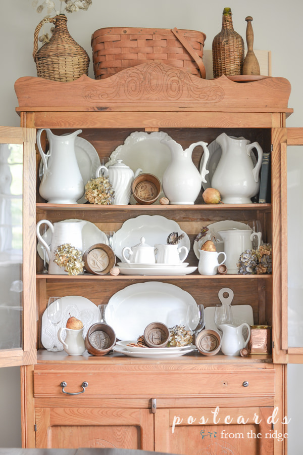 wooden butter molds and white ironstone pitchers and platter in antique oak hutch