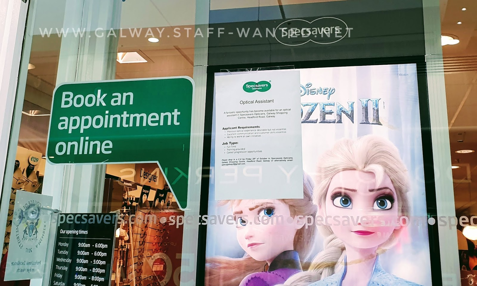 Specsavers shop-front with a visual display unit that has a Frozen poster, and showing opening hours Secsavers Galway Shopping Cetntre - opens 9am every day, closes 6pm Mon and Tues, 5pm Wed, Sat and Sun, and 8pm Thurs and Friday