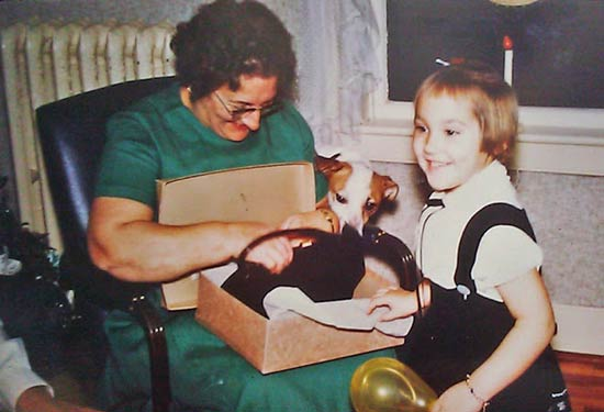 Kristi at approximately age 4 holding balloon. Her grandmother is opening a gift box containing a pocket book. A terrier also peers at gift.