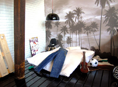 One-twelfth scale modern miniature loft space with a palm tree mural on the wall behind a futon bed with jeans draped over it.