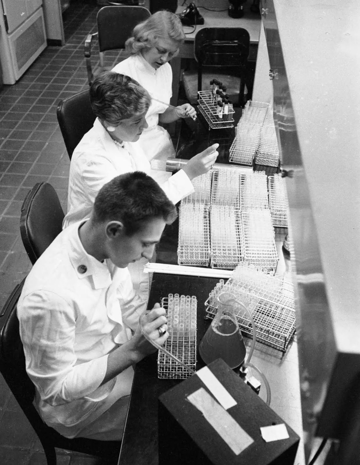 Researchers study the flu virus in a lab at Walter Reed Army Institute of Research, 1957.